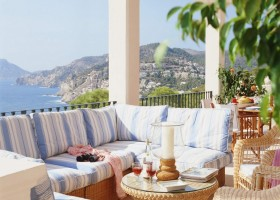 4-cozy-balcony-design-big-sofa-bench-seat-cushions-sea-view-striped-blue-and-white-textile-faux-ratten-coffe-table-wine-candles-magazines