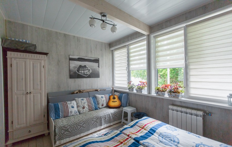 4-houseboat-float-house-interior-design-in-nautical-style-light-laminate-walls-larch-wood-floor-light-blue-accents-red-master-bedroom-bed-sofa-guitar-stool-radiator-wardrobe