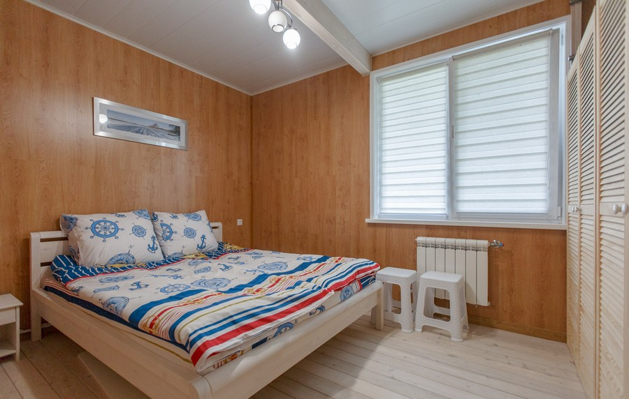 5-1-houseboat-float-house-interior-design-in-nautical-style-light-laminate-walls-larch-wood-floor-light-blue-accents-guest-bedroom-red-wooden-bed-stools-wardrobe-plantation-shutters-doors-radiator