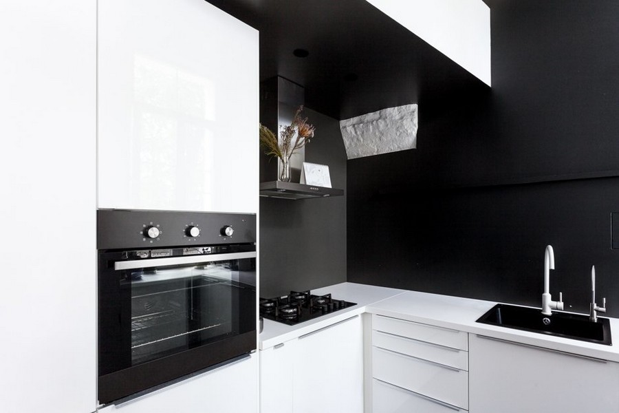 5-minimalist-style-ascetic-interior-painted-white-walls-brick-masonry-arched-ceiling-kitchen-set-by-IKEA-black-backsplash-white-cabinets-sink-built-in-oven-white-faucet