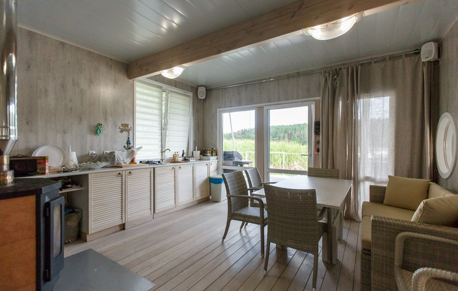 7-houseboat-float-house-interior-design-in-nautical-style-light-laminate-walls-larch-wood-floor-light-wooden-kitchen-set-cabinets-with-planatation-shutters-doors-sofa-dining-table-chairs-round-mirror-terrace-exit