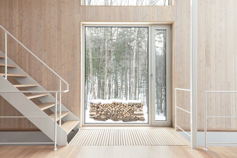 7-light-wood-house-interior-in-the-wood-Canada-panoramic-windows-light-airy-white-staircase-minimalist-ascetic-winter-forest-view-fire-wood-pile