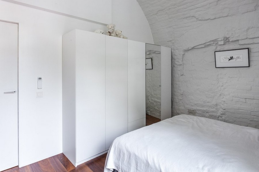 8-minimalist-style-ascetic-interior-painted-white-walls-brick-masonry-arched-ceiling-kid's-room-wardrobe-mirrored-door