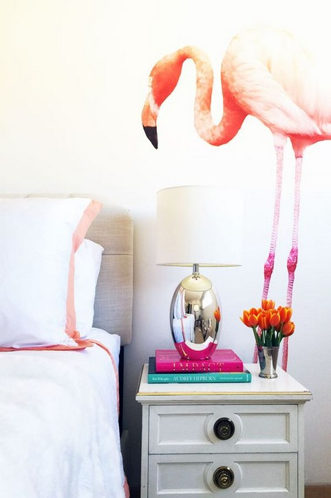 7-how-to-add-bright-color-to-home-interior-white-wall-bedroom-nightstand-flamingo-decor-pink-blue-books-orange-flowers