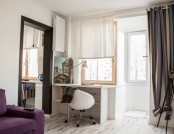 White-Walled Apartment with Black Curtains and Blue Accents, Partially Brick-Faced and Adorned with ...