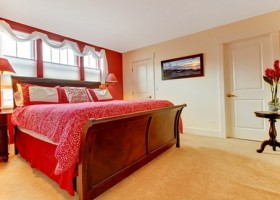 Master red romantic bedroom with beige carpet.