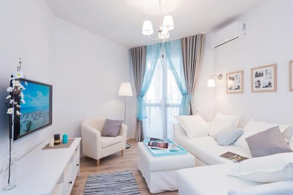 1-fresh-and-airy-white-and-blue-studio-apartment-interior-design-IKEA-sofa-ottoman-arm-chair