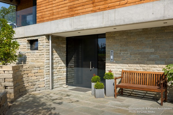 1-swiss-minimalist-modern-house-wood-and-concrete-entrance-door-potted-plants-wooden-bench-brick-wall