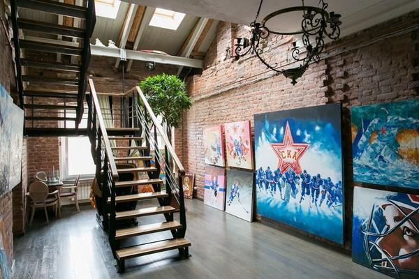 12-creative-interior-design-artist's-apartment-studio-artworks-paintings-political-sports-theme-brick-wall-staircase