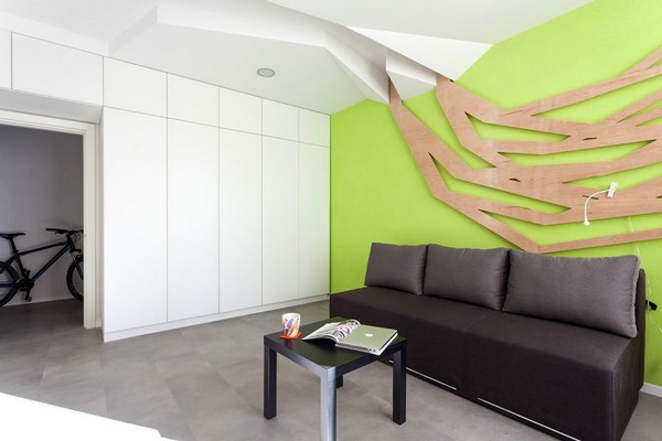 2-modern-ascetic-interior--living-room-with-white-walls-black-sofa-black-frameless-arm-chair-work-area-zone-white-glossy-cabinets-3D-geometrical-wooden-wall-panel-decor-bright-green-wall