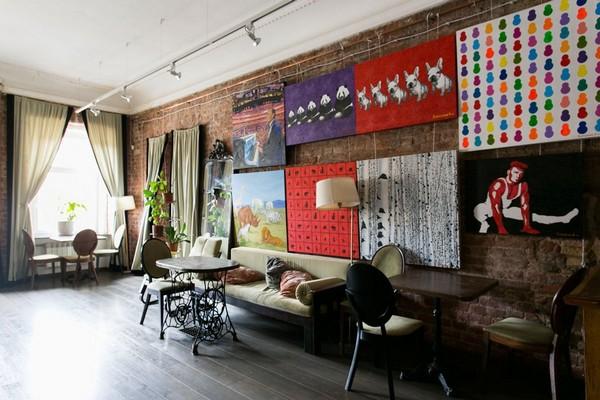 20-creative-interior-design-artist's-apartment-studio-artworks-political-sports-paintings-brick-walls-zinger-sewing-machine-pedestals-as-table-underframe