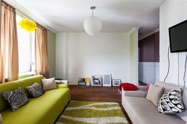 6-english-interior-style-open-concept-living-room-green-sofa-ball-lamp-shaggy-rug-carpet-pastel-green-walls-brick-wall