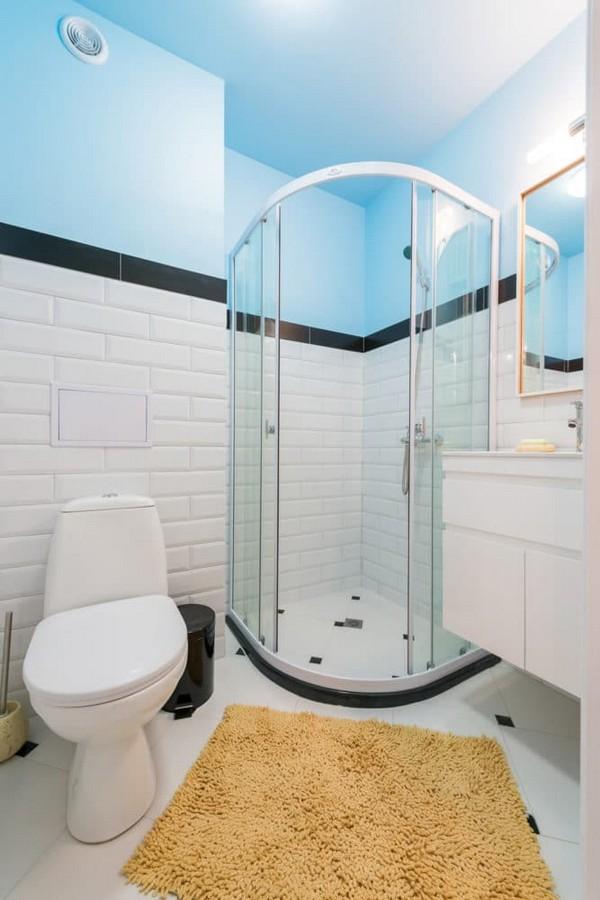 8-fresh-and-airy-white-and-blue-studio-apartment-bathroom-interior-design-kolo-toilet-bowl-linea-wash-basin-glass-shower-cabin