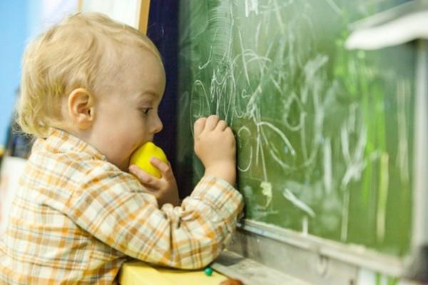 9-2-maria-monterssori-toddler-room-child-drawing-on-chalkboard-eating-lemon