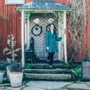 2-Scandinavian-Sweden-bohemian-boho-chic-style-old-wooden-orange-house-exterior-entrance-door-woman-hostess-stands-on-the-porch