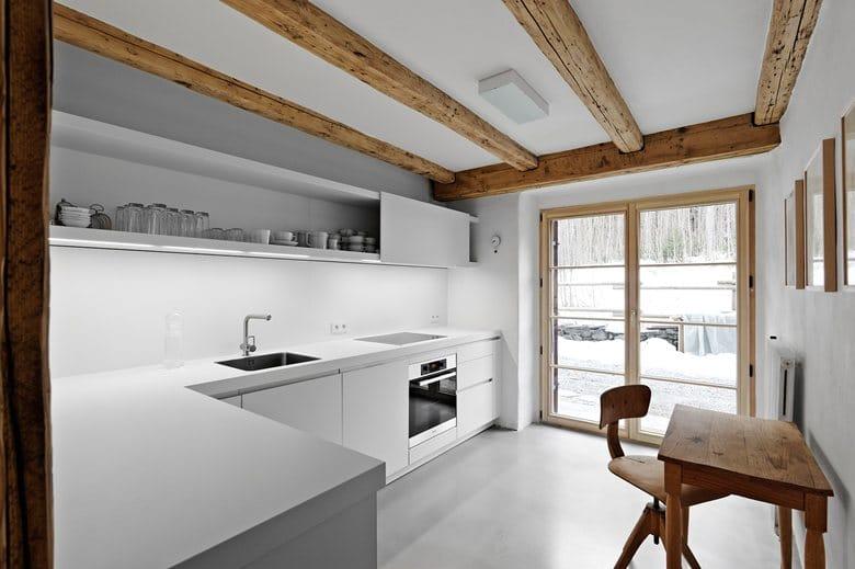 4-France-chalet-interior-design-Scandinavian-style-rough-wooden-beams-white-walls-modern-kitchen-set-minimalist-panoramic-windows-winter-view