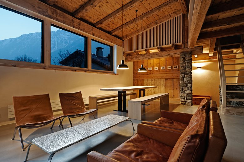 7-France-chalet-interior-design-Scandinavian-style-rough-wooden-beams-white-walls-dining-room-living-room-sofa-stone-mountain-view-soft-light