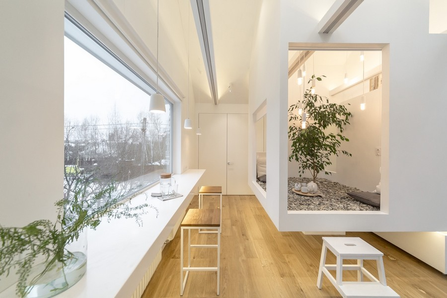 0-attic-floor-interior-design-in-contemporary-modern-style-open-space-modular-furniture-stools-soaring-cube-sloped-ceiling-skylights-light-floor-white-walls-unusual-architecture