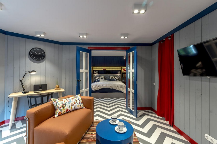 0-bright-gray-red-blue-attic-living-room-interior-design-wooden-boards-walls-painted-herringbone-parquet-floor-geometrical-furniture-TV-set-asyemmetrical-arm-chairs-rug-coffee-table-work-area-desk-hinged-lamp-bedroom