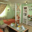 1-Provence-style-living-room-interior-design-green-mint-and-coral-colors-wooden-walls-sofa-sleeping-place-drapery-sloped-ceiling-floral-wallpaper-shelf-unit