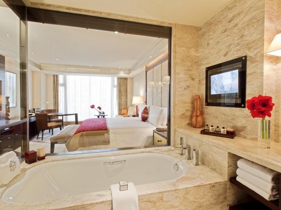 1-TV-set-in-bathroom-interior-design-beige-walls-glass-wall-to-bedroom