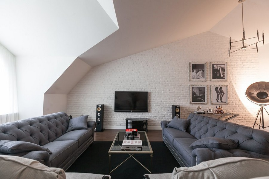 11-American-loft-style-attic-lounge-living-room-interior-design-capitone-sofas-floor-lamps-chandelier-white-faux-brick-wall-sloped-ceiling-coffee-table-blue-and-gray-carpet