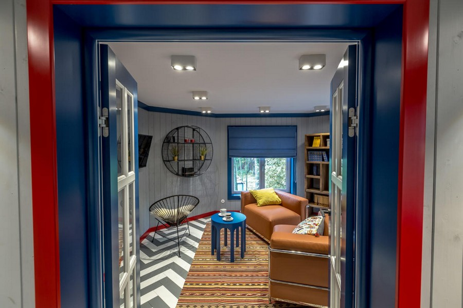 2-1-bright-gray-red-blue-attic-room-interior-design-wooden-boards-walls-painted-herringbone-parquet-floor-geometrical-furniture-asymmetrical-arm-chairs-shelving-unit-roman-blinds-rug-skirting-board-multicolored-doors