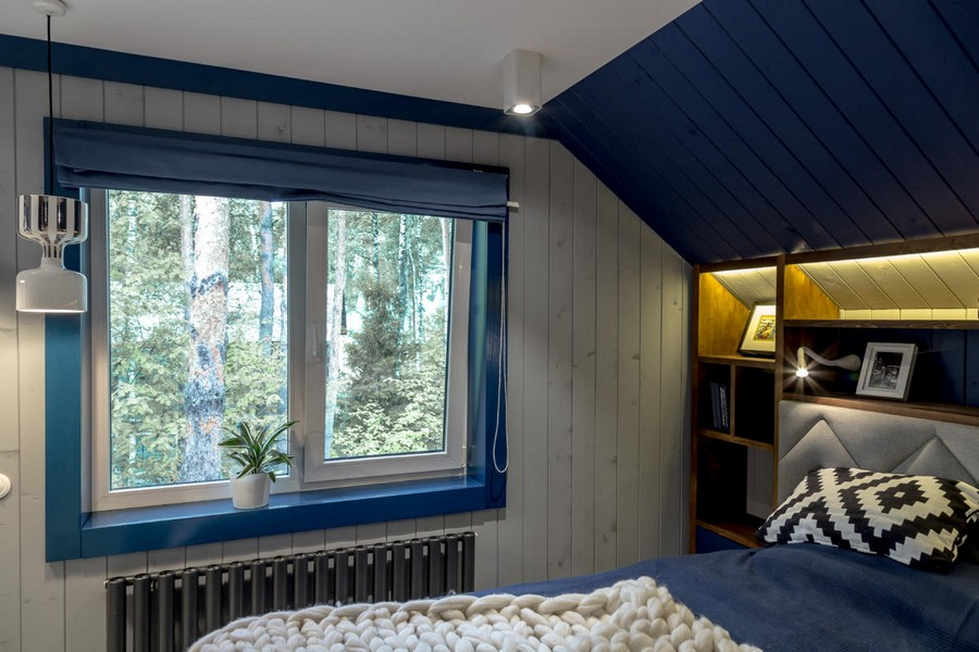 2-2-bright-gray-red-blue-attic-bedroom-interior-design-wooden-boards-walls-painted-window-frame-sloped-ceiling-bed-shelves-recess-decorative-pillow