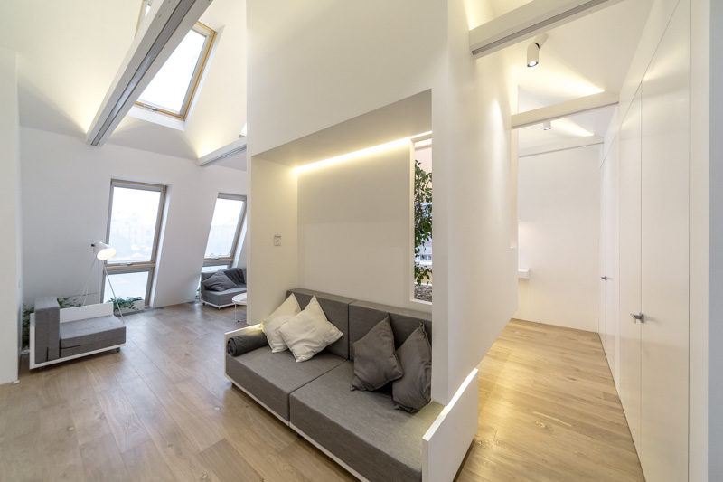 2-attic-floor-interior-design-in-contemporary-modern-style-open-space-modular-furniture-sofas-soaring-cube-sloped-ceiling-skylights-light-floor-white-walls-gray-furniture