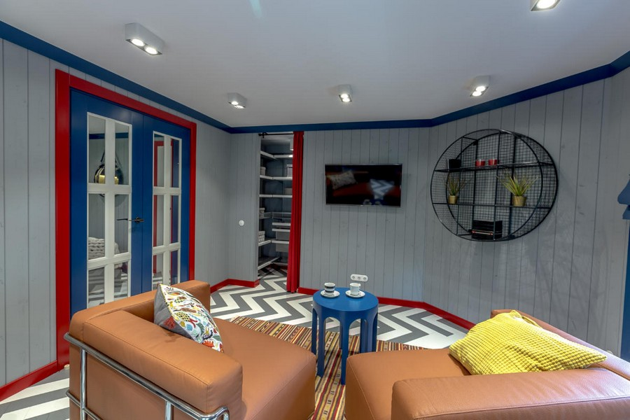 3-1-bright-gray-red-blue-attic-room-interior-design-wooden-boards-walls-painted-herringbone-parquet-floor-geometrical-furniture-asymmetrical-arm-chairs-shelving-unit-skirting-board-multicolored-doors-walk-in-closet