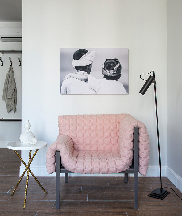 3-minimalist-style-studio-apartment-interior-design-open-concept-white-walls-living-room-pale-pink-asymmetrical-Inga-Sempe-arm-chair-floor-lamp-black-and-white-photo-coffee-table