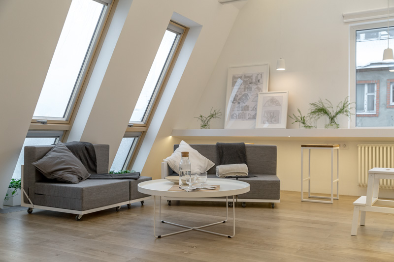 4-attic-floor-interior-design-in-contemporary-modern-style-open-space-modular-furniture-sofas-sloped-ceiling-skylights-light-floor-white-walls-gray-furniture