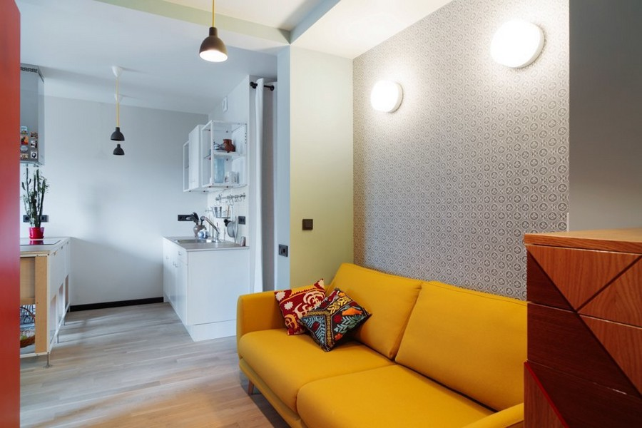 0-bachelor's-interior-design-open-concept-living-room-kitchen-light-blue-walls-yellow-sofa-red-accents-wall-light-oak-parquet-BoConcept-chest-of-drawers-wall-lamps
