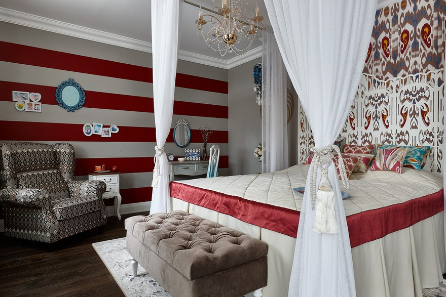 0-contemporary-style-bedroom-interior-design-with-oriental-Central-Asian-Uzbek-motifs-canopy-bed-ikat-pattern-wallpaper-white-red-gray-blue-accents-pomegranate-stripy-dressing-table-ottoman-arm-chair-chandelier