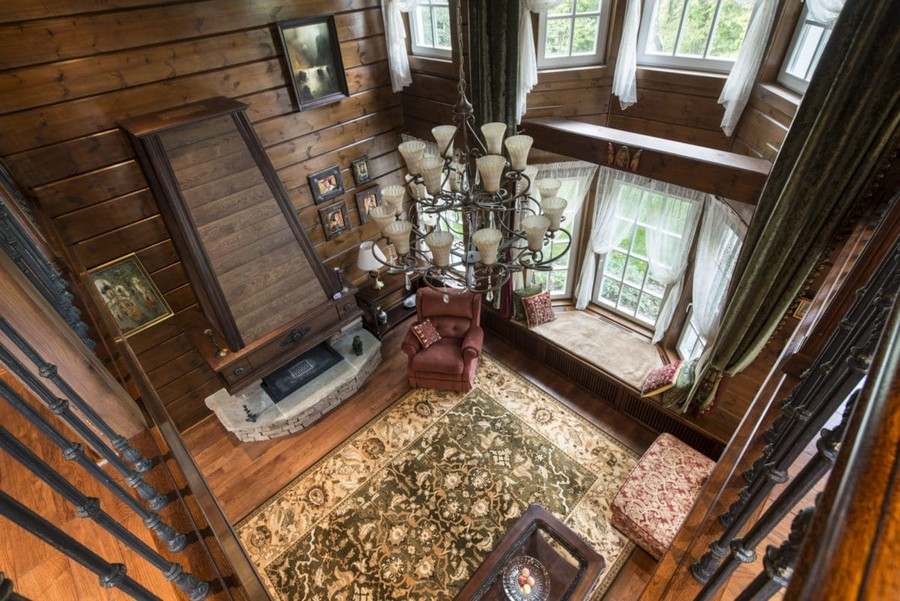 1-2-log-timber-wooden-house-interior-design-walls-big-panoramic-windows-overdrapery-drapery-sheer-curtains-gallery-open-to-below-second-floor-floral-sofa-green-pink-brown-living-room-lounge-fireplace