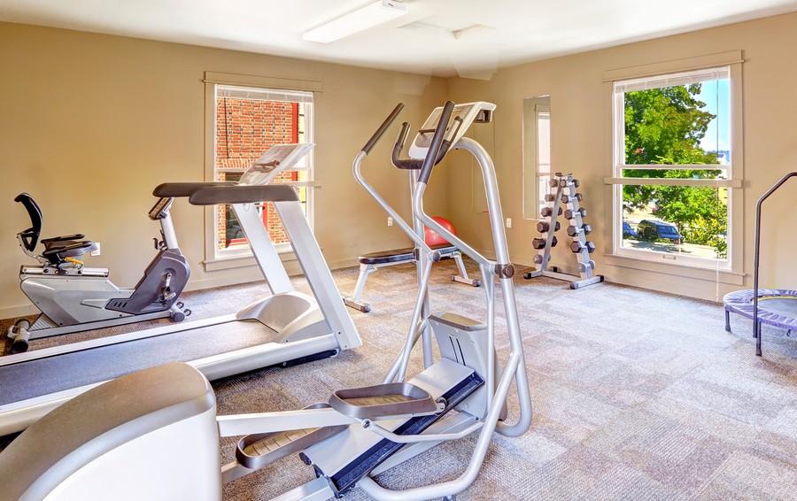1-home-gym-interior-design-light-neutral-colors-windows-fitness-exercise-equipment-beige-walls-racetrack