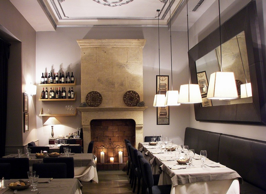 2-1-Convivium-restaurant-cafe-bar-in-Milan-Italy-interior-design-traditional-style-gray-blue-beige-elegant-faux-fireplace-candles-wine-racks-low-pendant-lamps