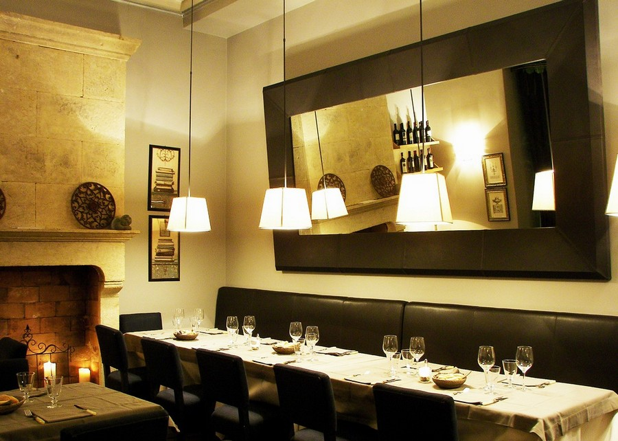 2-2-Convivium-restaurant-cafe-bar-in-Milan-Italy-interior-design-traditional-style-gray-blue-beige-elegant-faux-fireplace-candles-wine-racks-mirror-low-pendant-lamps-chairs-long-table-sofa