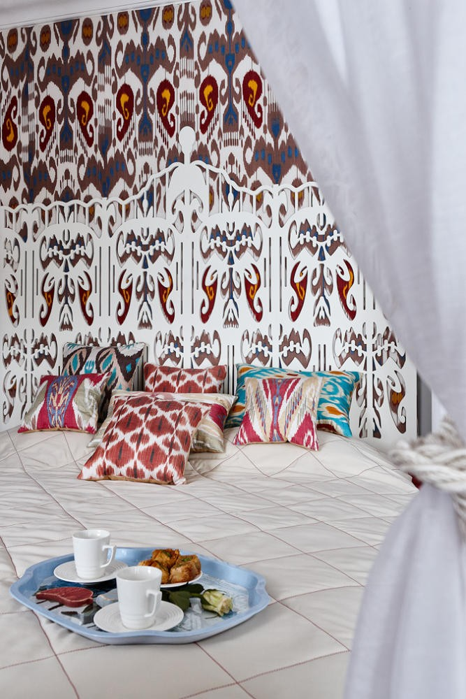 2-2-contemporary-style-bedroom-interior-design-with-oriental-Central-Asian-Uzbek-motifs-canopy-bed-ikat-pattern-wallpaper-white-red-gray-blue-accents-pomegranate-carved-headboard-felt-lamp-ombre-effect-throw-pillows