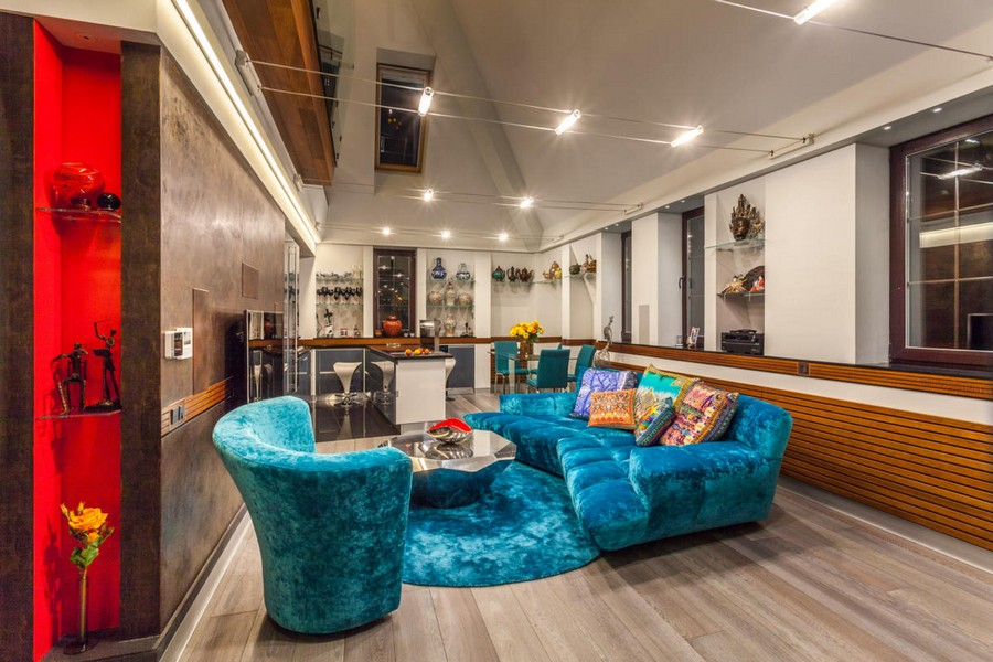 2-3-contemporary-style-interior-design-living-room-lounge-gray-brushed-parquetry-velvet-blue-sofa-round-carpet-coffee-table-open-concept-kitchen-dining-room-cable-lights-recessed-shelves-island-red-bowl-skylights