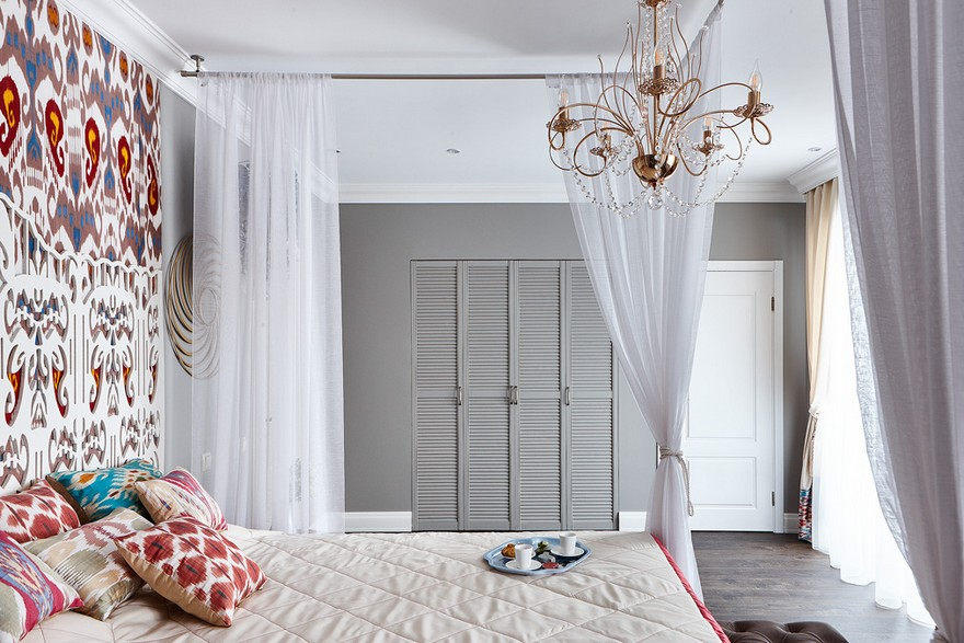 3-4-contemporary-style-bedroom-interior-design-with-oriental-Central-Asian-Uzbek-motifs-canopy-bed-ikat-pattern-wallpaper-white-red-gray-blue-accents-pomegranate-chandelier-built-in-closet-carved-headboard-pillows