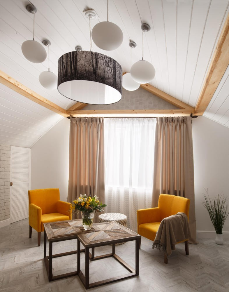 3-contemporary-style-attic-interior-sloped-ceiling-white-walls-wooden-coffee-table-metal-framework-yellow-arm-chairs-living-room-naturalistic-beige-curtains-corkwood-floor-faux-beams-group-of-lamps-forest-motifs