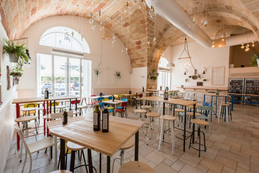 4-1-Pescaria-restaurant-cafe-bar-in-Milan-Italy-interior-arched-brick-masonry-ceiling-light-wood-tables-multicolor-chairs-and-stools-blue-red-yellow