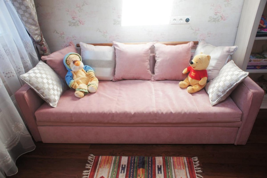 4-3-kids-toddler-girl's-bedroom-room-interior-design-gray-and-pink-sofa-throw-pillows-winnie-the-pooh-toys-velvet-floral-wallpaper-multicolor-rug