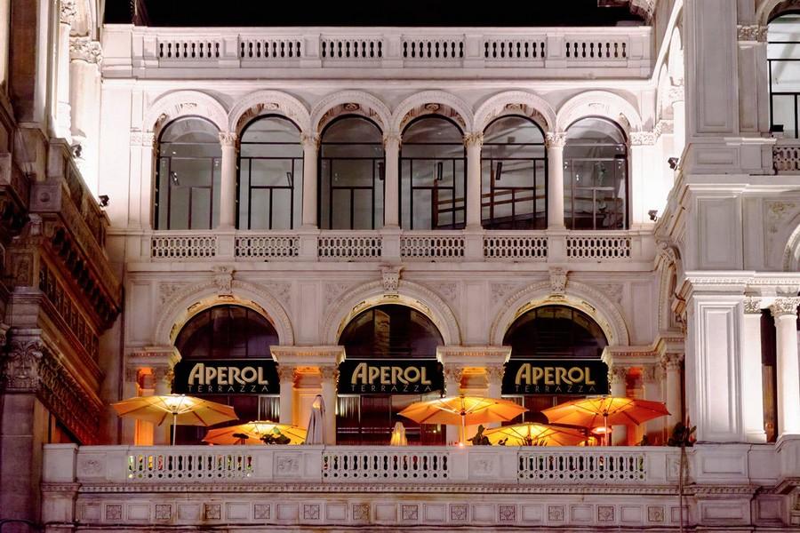 6-1-La-Terrazza-Aperol-restaurant-cafe-bar-in-Milan-Italy-exterior-historic-building-arched-windows-open-terrace-bright-orange-sunshade