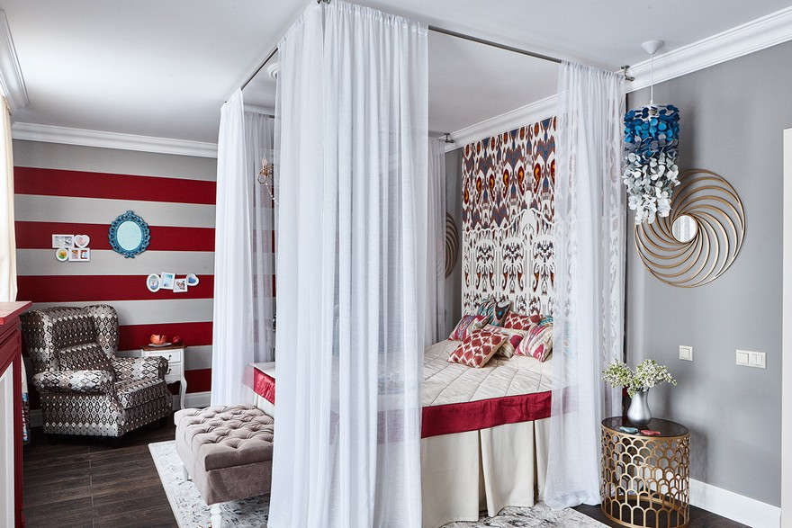 6-contemporary-style-bedroom-interior-design-with-oriental-Central-Asian-Uzbek-motifs-canopy-bed-ikat-pattern-stripy-wallpaper-white-red-gray-blue-accents-pomegranate-ottoman-felt-lamp-ombre-effect-arm-chair-mirror