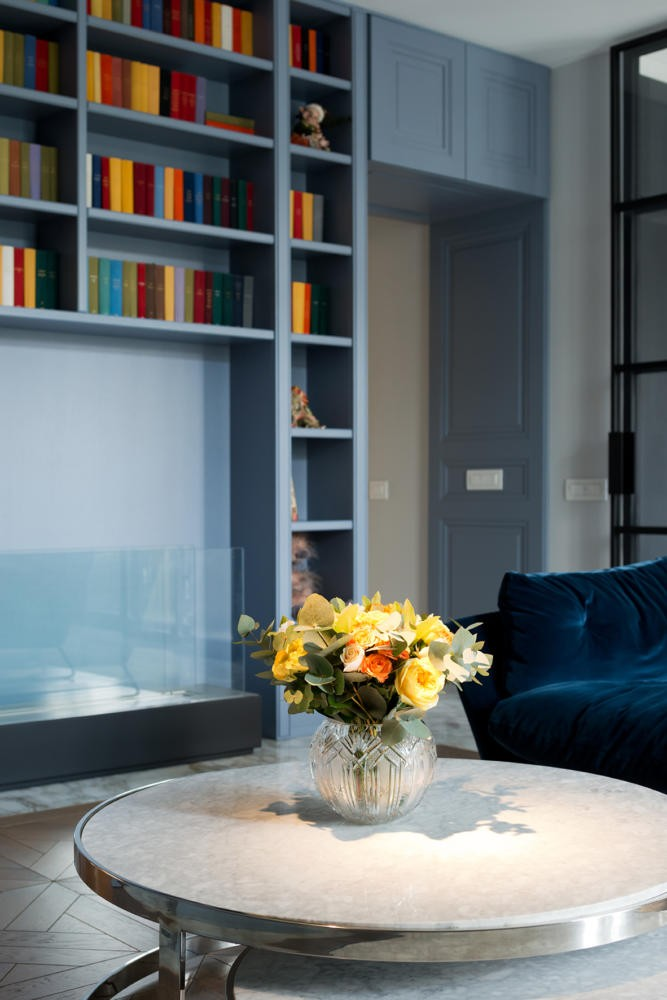 0-American-style-interior-living-room-lounge-bio-fireplace-home-library-book-shelves-blue-velvet-sofa-wall-panelling-metal-round-coffee-table-flowers-vase