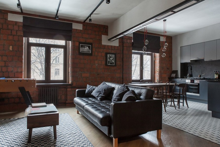 0-bachelor's-pad-interior-design-loft-style-brutal-open-concept-kitchen-set-dining-living-room-building-bricks-masonry-wall-leather-sofa-black-track-lights-bulbs-exposed-wires-soccer