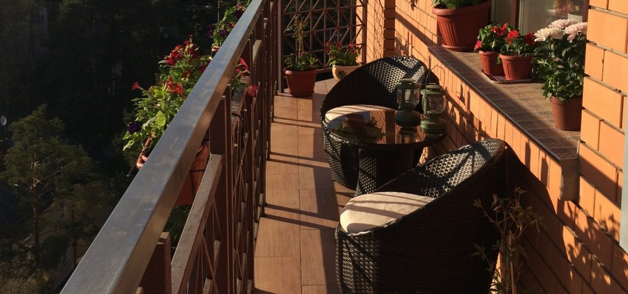 0-brown-open-balcony-interior-exterior-masonry-wall-wicker-furniture-coffee-table-chairs-flower-pots-boxes-mediterranean-style-tiles-sill