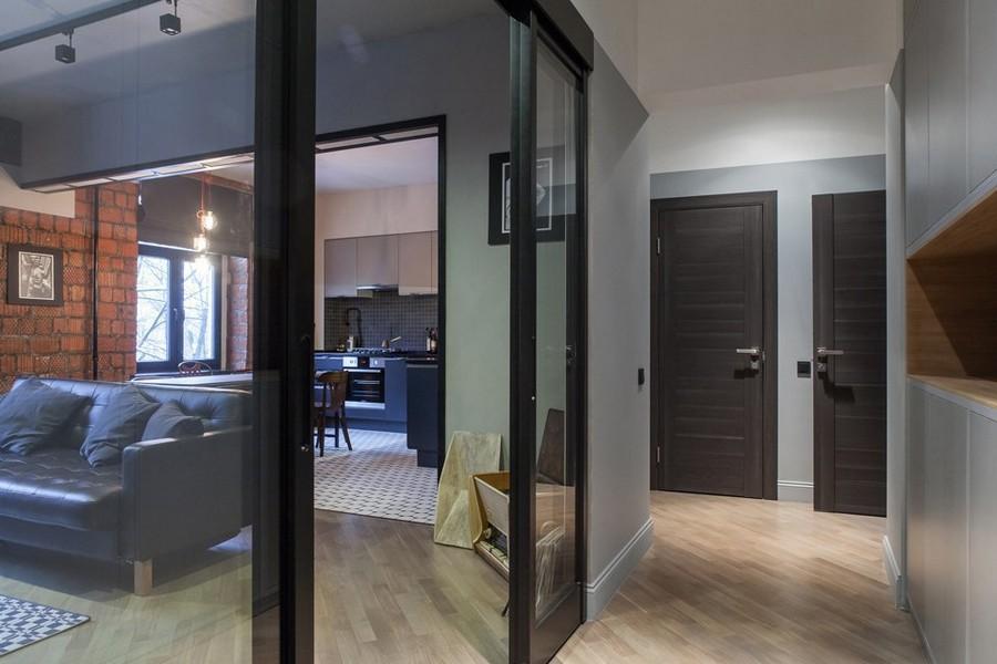 1-1-bachelor's-pad-interior-design-loft-style-brutal-open-concept-living-room-kitchen-corridor-glass-sliding-door-dark-doors-light-laminate-floor-gray-walls